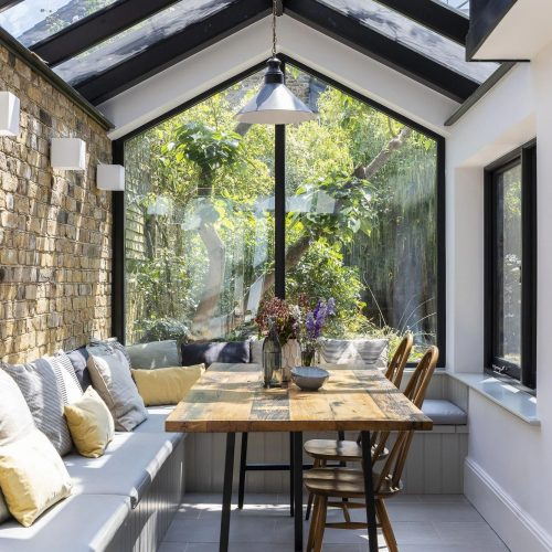 Peaked roof sunroom with glass and stone