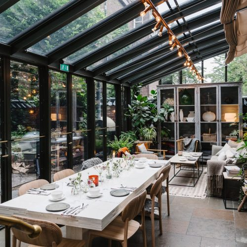 Glass sunroom with dining table and plants